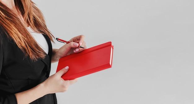 Frauengeschäftsdame im schwarzen anzug mit rotem tagebuchplaner in der hand
