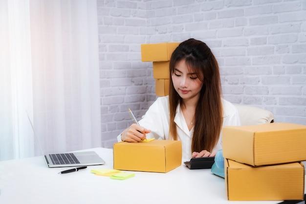 Frauengeschäftsinhaber-schreibadresse auf verpackungskasten am arbeitsplatz im hauptbüro