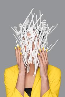 Frauengesicht bedeckt mit plastikgeschirr, das neben einer ultimativen grauen wand steht