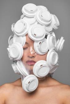 Frauengesicht, das mit weißen plastikdeckeln bedeckt wird