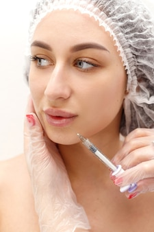 Frauengesicht in der medizinischen kappe mit spritze an den lippen