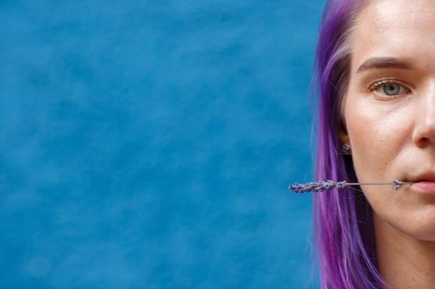 Frauengesicht mit lavendelstock im mund