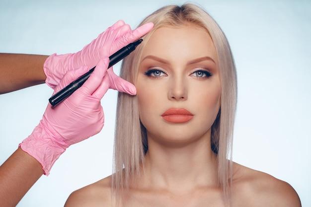 Frauengesicht und arzthände mit konzept der plastischen chirurgie des bleistifts