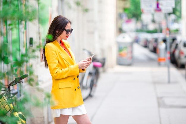 Frauengespräch durch ihren smartphone in der stadt.