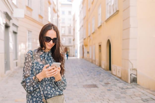 Frauengespräch durch ihren smartphone in der stadt