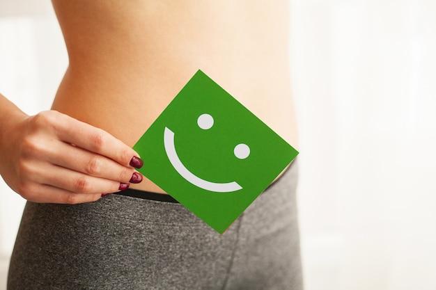 Frauengesundheit. nahaufnahme der gesunden frau mit dünnem körper des schönen sitzes im schwarzen schlüpfer, der green card mit glücklichem smiley face in hands hält. magengesundheit und gute verdauungskonzepte.