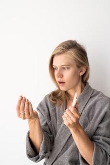 Frauengesundheit. spa und wellness. junge frau in grauen bademänteln, die an haarausfall leidet. fokus auf den vordergrund