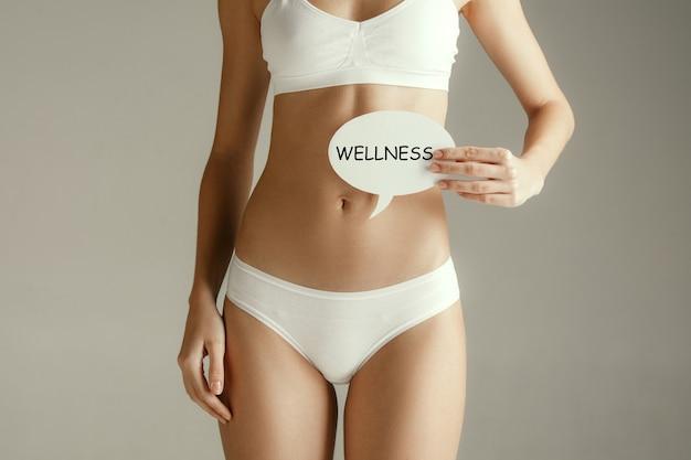 Frauengesundheit. weibliches modell, das karte nahe magen hält. junges erwachsenes mädchen mit papier mit wort wellness lokalisiert auf grauem studiohintergrund. körperteil ausschneiden. medizinisches problem und lösung.