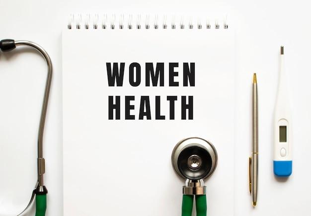 Frauengesundheitstext geschrieben in einem notizbuch, das auf einem schreibtisch und einem stethoskop liegt. medizinisches konzept.