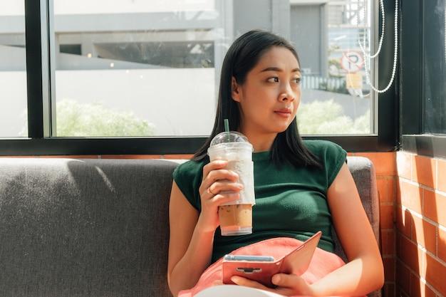 Frauengetränk gefrorener kaffee und benutzen ihren smartphone
