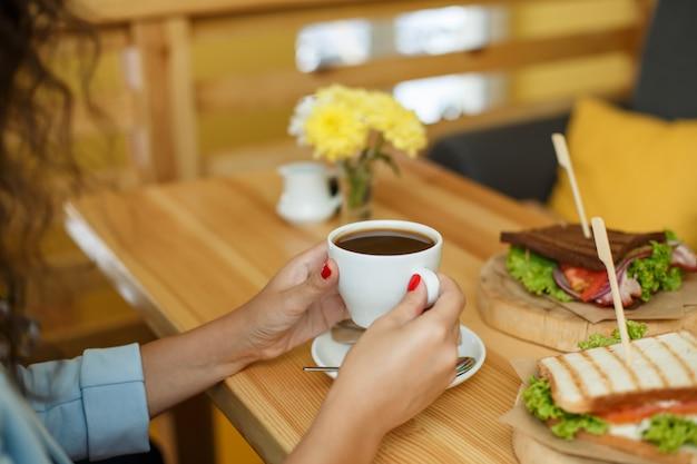 Frauengriff ein tasse kaffee am backgroud holztisch, auf dem ein sandwich liegt