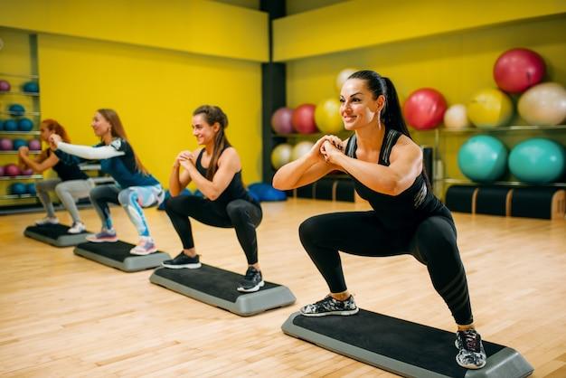Frauengruppe auf schritt aerobic-training. weibliche sportteamarbeit im fitnessstudio. fit klasse, fitnessübung in bewegung