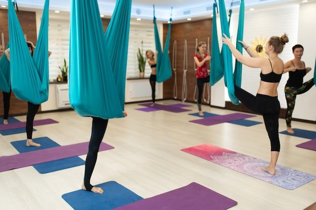 Frauengruppe, die das fliegenyoga ausdehnt übungen in der turnhalle tut