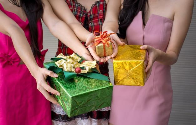 Frauengruppe, die geschenkbox in den händen hält