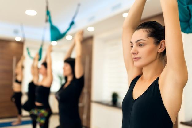 Frauengruppe, die yogaübungen in der turnhalle tut