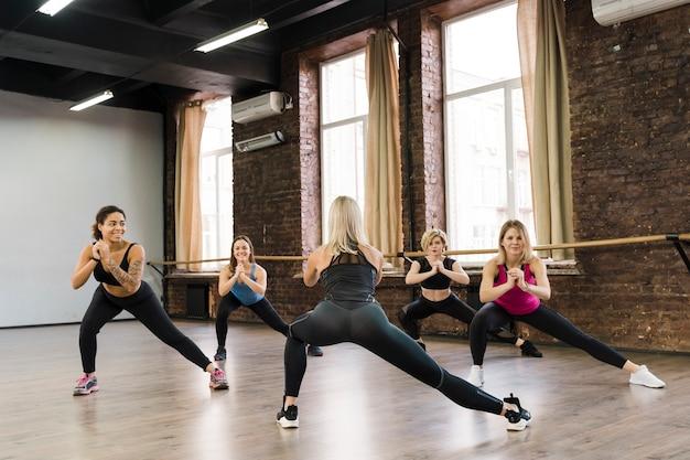 Frauengruppe, die zusammen an der turnhalle trainiert