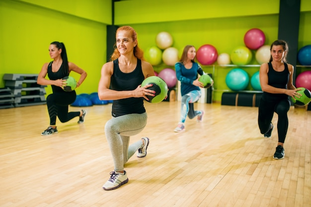 Frauengruppe mit bällen in bewegung, fitnesstraining. weibliche sportteamwork im fitnessstudio. fitnesstraining, aerobic