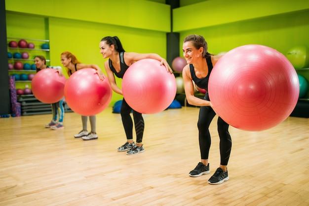 Frauengruppe mit großen bällen, die übung, fitness tun