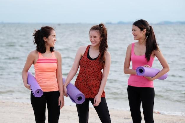 Frauengruppe, welche die yogamatte steht auf strandhintergrund, wellness, gesundheitslebensstil hält