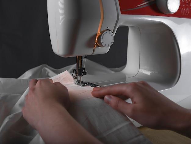 Frauenhände an der nähmaschine während des arbeitsprozesses mit stoff.