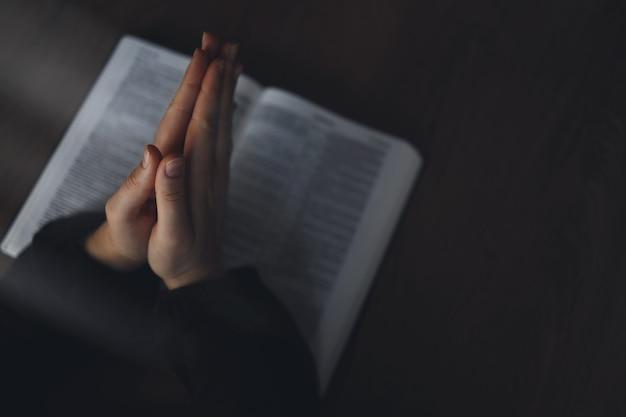Frauenhände auf bibel. sie liest und betet über die bibel in einem dunklen raum über einem holztisch.