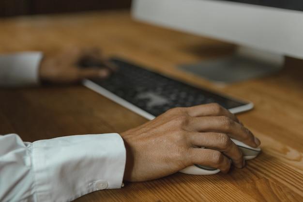 Frauenhände auf tastatur und halten der computermaus, die von den pc-fachleuten sitzt, die beim zusammenarbeiten im modernen büro kommunizieren.