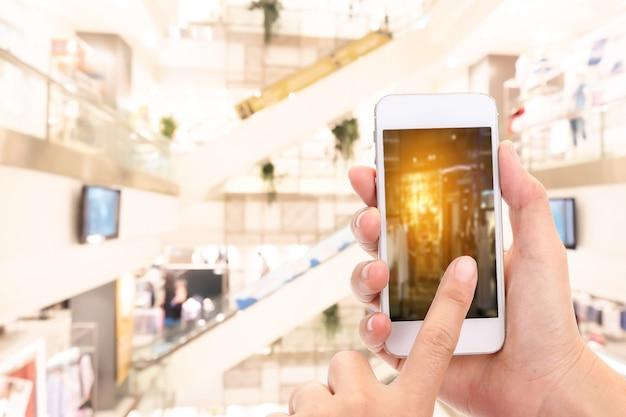 Frauenhände aufnehmen eines bildes mit einem smartphone im einkaufszentrum mit unscharfem bild des bekleidungsgeschäfts.