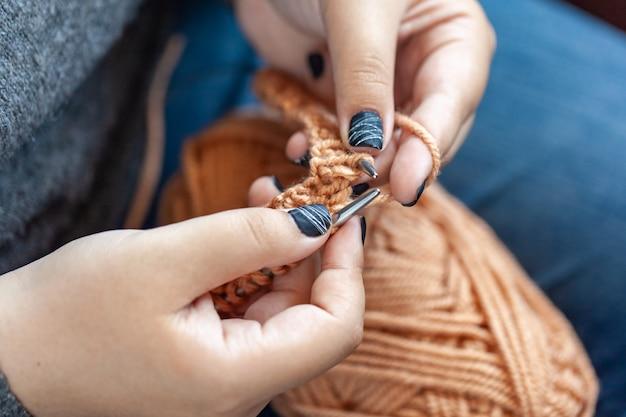 Frauenhände aus bunter wolle gestrickt. handstricken