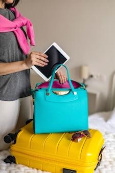 Frauenhände bereiten reisereise vor, die tablet-pc in handtasche packt, die gepäck im schlafzimmer verpackt