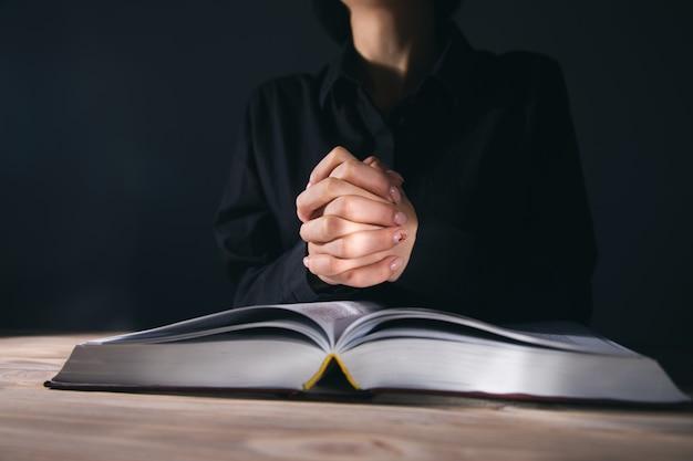 Frauenhände beten mit einer bibel in einem dunklen raum