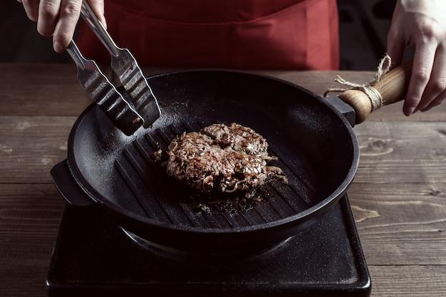 Frauenhände des chefs mit einer grillwanne und einem gebratenen stück fleisch.