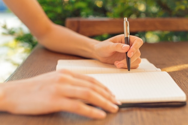 Frauenhände, die anmerkungen in einem notizblock auf einer cafétabelle machen