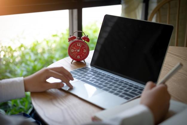 Frauenhände, die auf computertastatur schreiben und schreiben anmerkung, geschäftszeitplan und frist