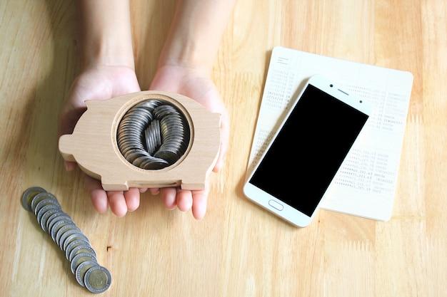 Frauenhände, die auf dem tisch sparschweinholz und einen hintergrund des smartphone halten