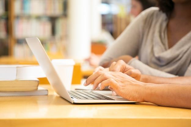 Frauenhände, die auf laptop schreiben