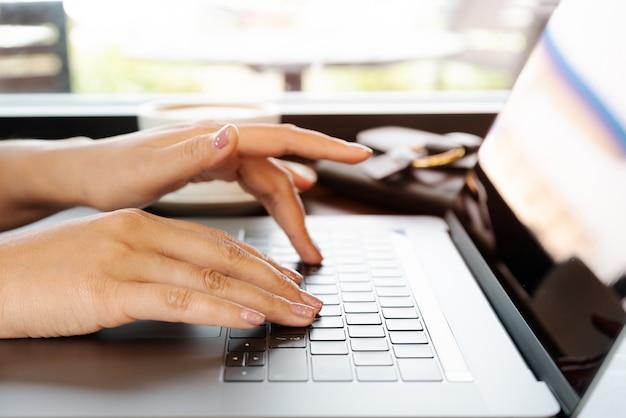 Frauenhände, die auf laptoptastatur schreiben. frau, die im büro mit kaffee arbeitet