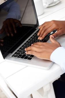 Frauenhände, die auf laptoptastatur schreiben