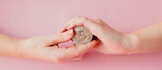 Frauenhände, die bitcoin auf einem rosa symbol des virtuellen geldes halten.