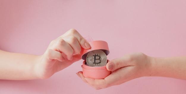 Frauenhände, die bitcoin in der rosa geschenkbox auf einem rosa symbol des virtuellen geldes halten.