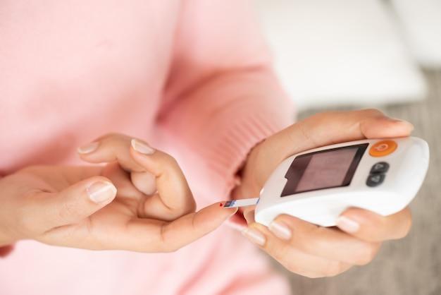 Frauenhände, die blutzuckerspiegel durch glukosemessgerät für diabetes-tester überprüfen