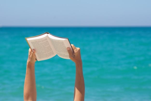 Frauenhände, die buch halten und auf dem meer lesen.
