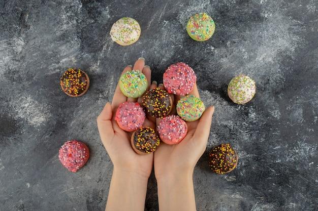 Frauenhände, die bunte süße donuts mit streuseln halten.