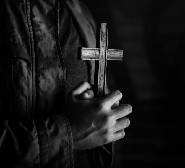 Frauenhände, die das kreuz beten für gott halten