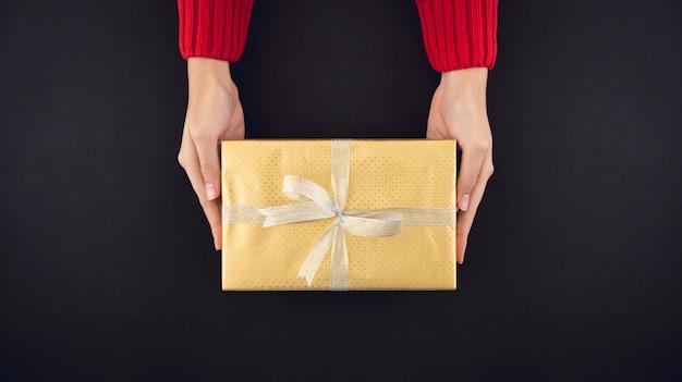 Frauenhände, die die christsmas geschenkbox eingewickelt mit glänzendem goldenem papier geben