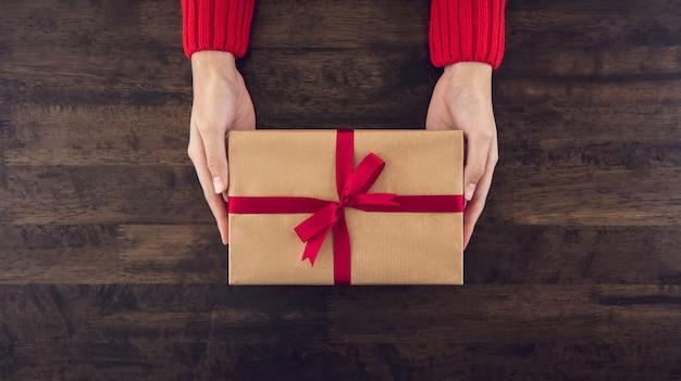 Frauenhände, die die christsmas geschenkbox eingewickelt mit hellbraunem papier geben