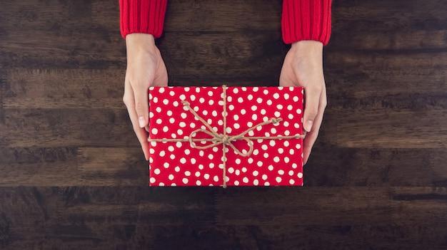 Frauenhände, die die christsmas geschenkbox eingewickelt mit roter punktierter draufsicht des papiers geben