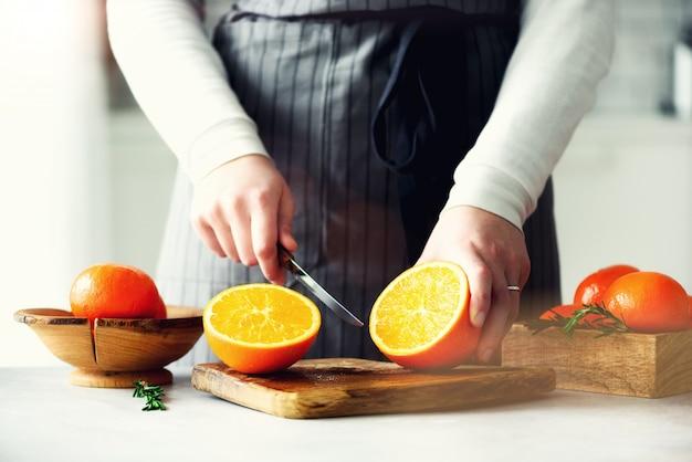 Frauenhände, die die orange, zitrusfrucht schneiden.