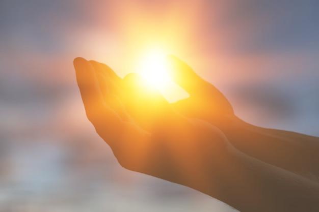 Frauenhände, die die sonne im morgengrauen halten. freiheit und spiritualität konzept.