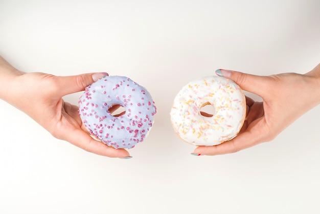 Frauenhände, die donuts halten, draufsicht. mädchen, das wahl wählt. süße donuts für dich.