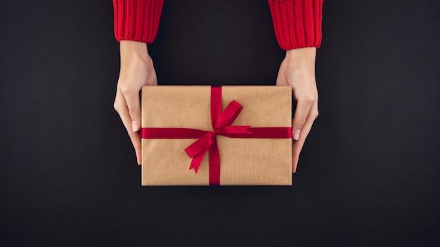 Frauenhände, die draufsicht der christsmas geschenkbox über schwarzen hintergrund geben